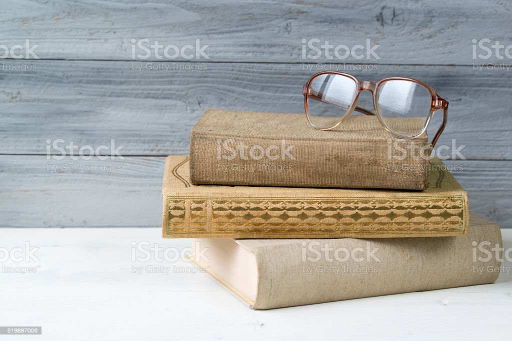 Stack of old books and reading glasses on wooden background stock photo