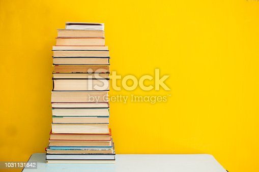 480762174istockphoto Stack of old books isolated on yellow background 1031131642