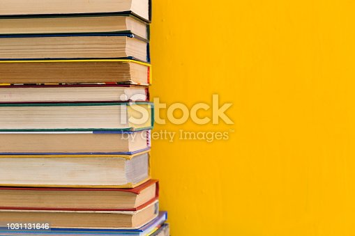 480762174istockphoto Stack of old books isolated on yellow background 1031131646