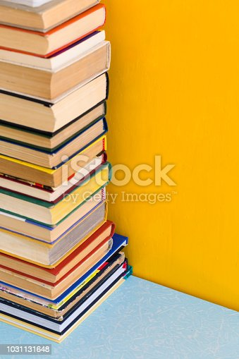 480762174istockphoto Stack of old books isolated on yellow background 1031131648