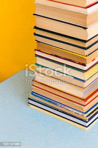 480762174istockphoto Stack of old books isolated on yellow background 1031131660