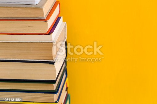480762174istockphoto Stack of old books isolated on yellow background 1031131664