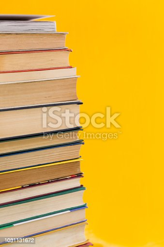 480762174istockphoto Stack of old books isolated on yellow background 1031131672
