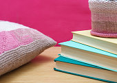 stack of books on a wooden shelf pink background and knitted decorative pillow. home decor