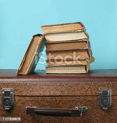 istock Stack of old books on retro suitcase on a blue background 1127836828