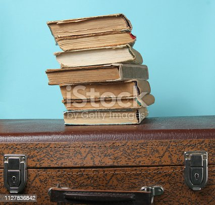 istock Stack of old books on retro suitcase 1127836842