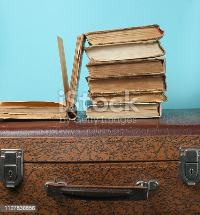 istock Stack of old books on retro suitcase 1127836856