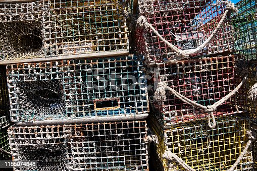 Well used, old and rusty colorful lobster traps stacked on the pier in Old Port, Portland, Maine Typical New England (Maine) scenery and lifestyle.