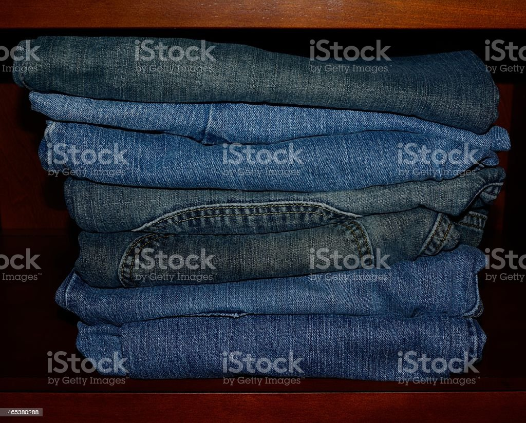 Stack of Old Folded Blue Jeans on a Shelf stock photo