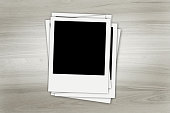 istock Stack of old instant photos at grunge wooden background 1310402985