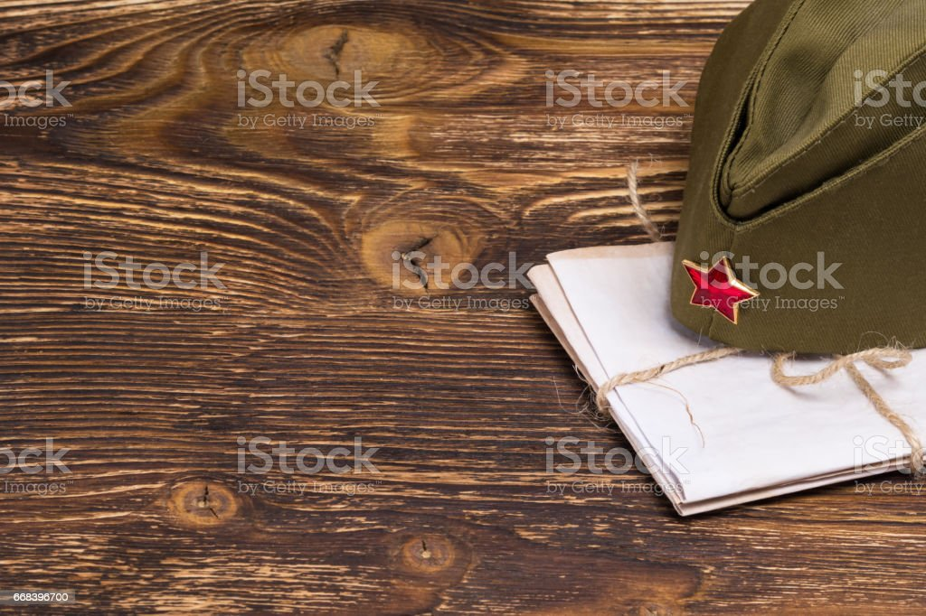 stack of old letters under the military cap on the table stock photo