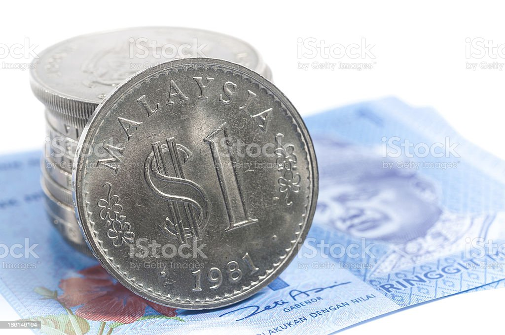 Stack of old Malaysia coins on new Bank Notes stock photo