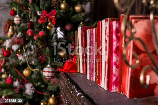 1057183432 istock photo Stack of old vintage books, Winter decoration. decoration of the shelf for the new year or Christmas. candles, Christmas tree, books, craft present gift box and christmas tree decoration on wooden 1051588130