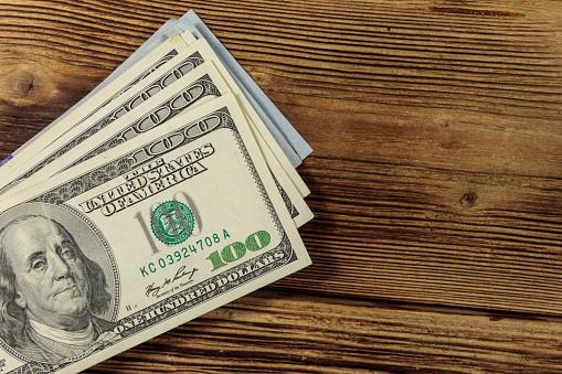 Stack Of One Hundred Dollars Bills On Wooden Desk — стоковые фотографии и другие картинки 100 американских долларов