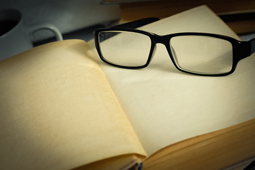 Stack of open vintage books with glasses and  cup of tea on  table