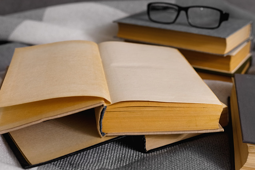 Stack of open vintage books with glasses on  table