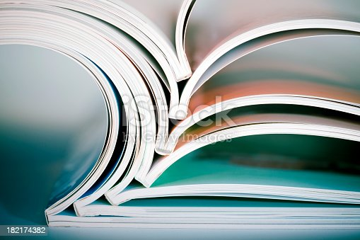 Abstract shot of open magazines stack on table. Macro shot with shallow DOF