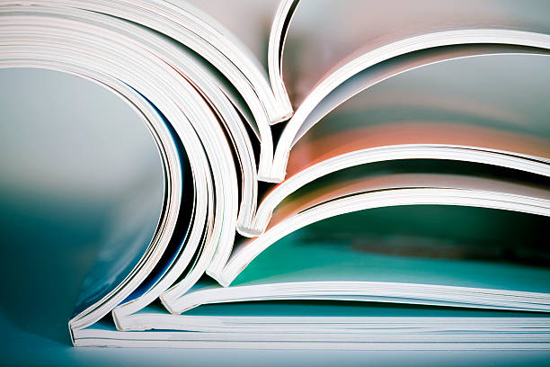 stack of opened magazines - publication stock pictures, royalty-free photos & images