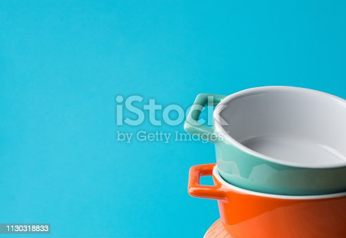 Stack of orange and turquoise ceramic cocottes on white wood table blue wall background. Cooking baking cookware concept. Scandinavian kitchen interior. Workshop poster template