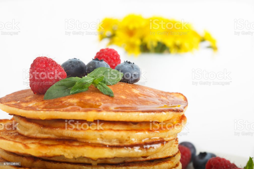 Stack of pancakes decorated with bluberries, raspberries and mint leaves stock photo