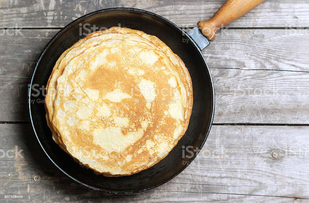 Stack of pancakes on a cast-iron frying pan. stock photo