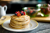 A pretty tall stack of pancakes topped with fresh berries; focus is on the pancakes and there are bowls of berries and a syrup pitcher in the background.