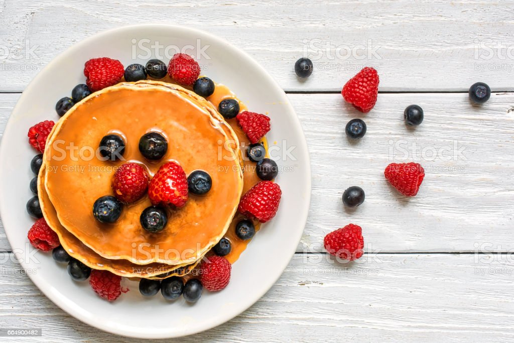 stack of pancakes with fresh berries and caramel sauce stock photo
