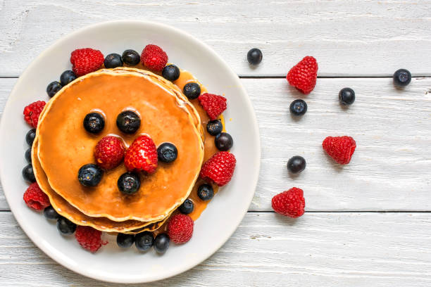 stack of pancakes with fresh berries and caramel sauce - pancake foto e immagini stock