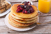 Stack of pancakes on a plate with glass of orange juice and breakfast bars