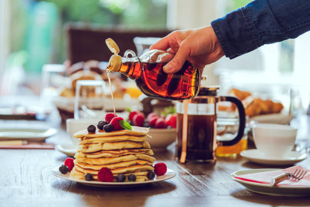 stack of pancakes with maple syrup, berries and fresh coffee - maple syrup stock photos and pictures