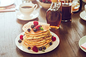 Stack of Pancakes with Maple Syrup, Berries and Fresh Coffee