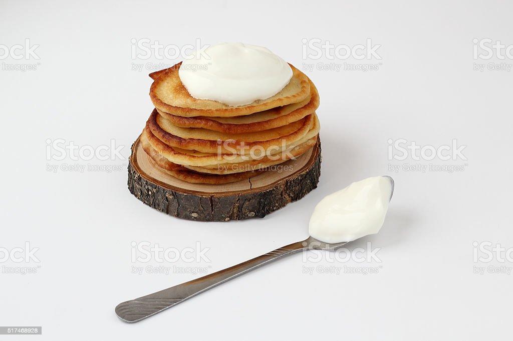 Pile de crêpes avec de la crème aigre sur la pièce en bois - Photo