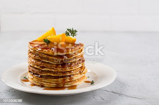 istock Stack of pancakes with with orange and sprinkled caramel  syrup 1012506286