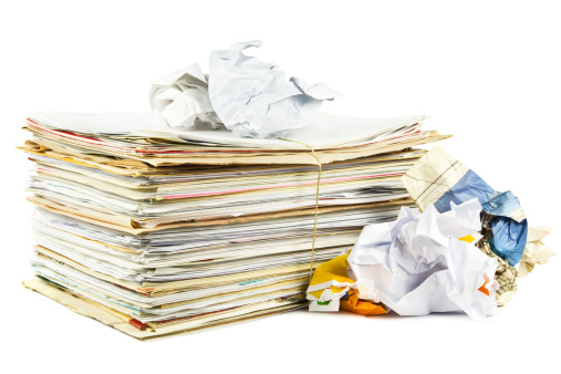A stack of paper beside crumpled papers