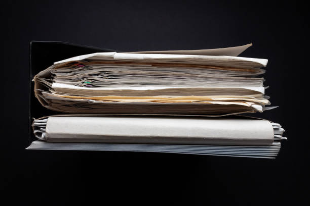 stack of paper documents with paper clips on a black background stock photo