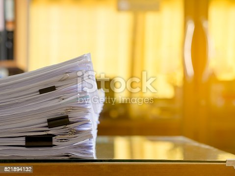 istock Stack of paper files on work desk in office. Flare light. 821894132