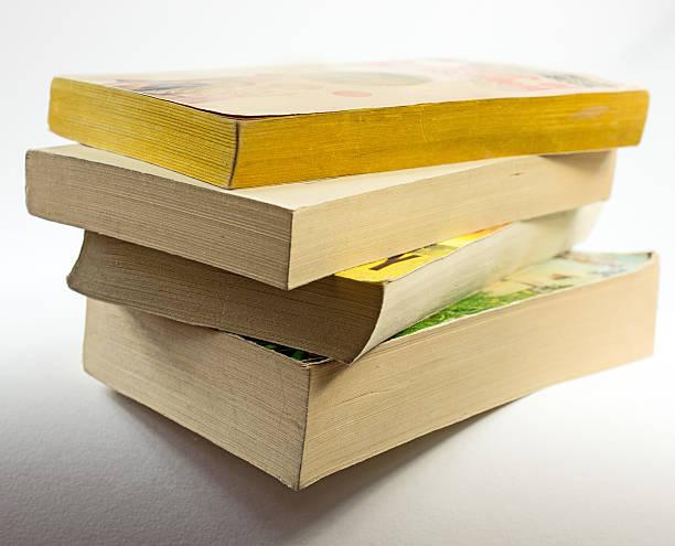 stack of paperback books with shadow on white,  copy space - brochura - fotografias e filmes do acervo