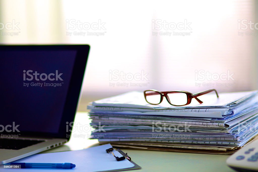 stack of papers on the desk with  computer stock photo
