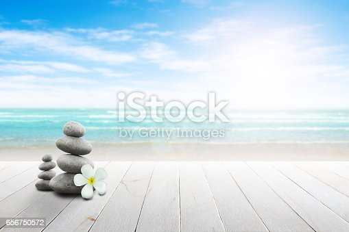 istock Stack of pebble stones and Plumeria wooden surface. 656750572