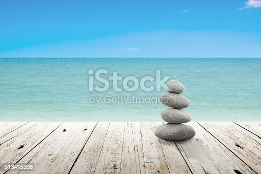 istock Stack of pebble stones at the beach on a wooden. 513415398