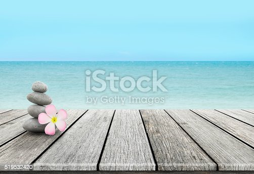 istock Stack of pebble stones at the beach on a wooden 519532420