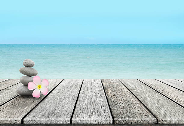 stack of pebble stones at the beach on a wooden - stack rock stock pictures, royalty-free photos & images