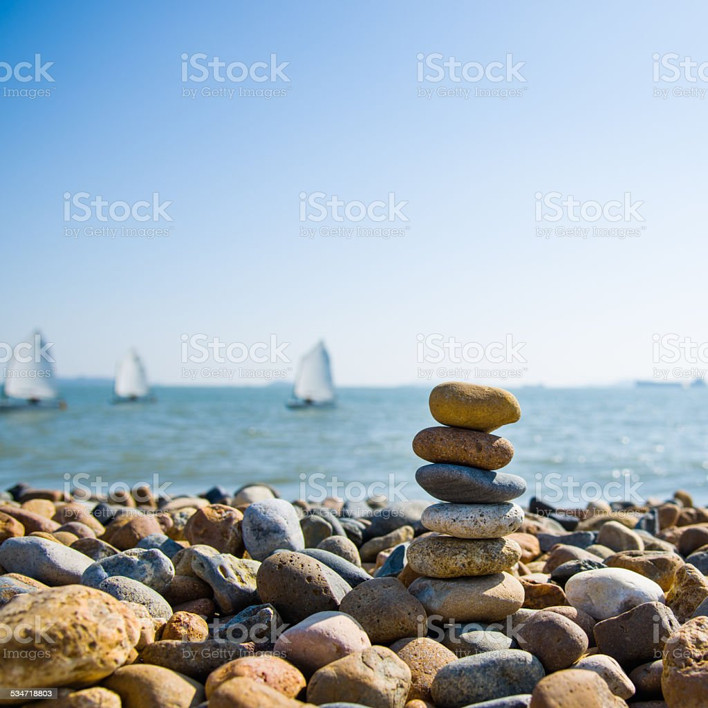 Stack of pebbles and sailboat stock photo