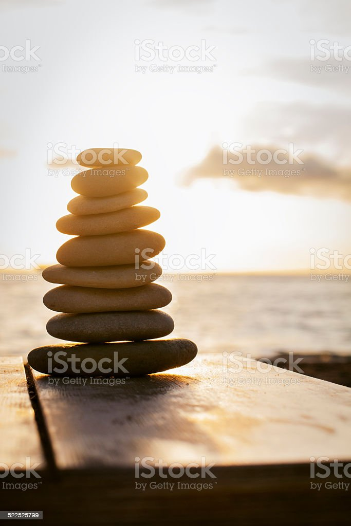Stack of pebbles on a table at sunset . Balance. stock photo