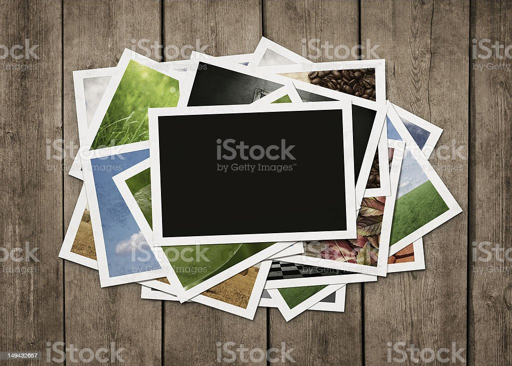 Stack of photos at wooden background stock photo