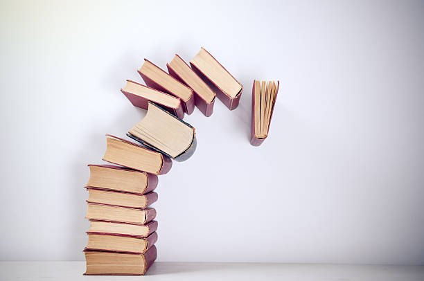 A stack of piled books toppling over stock photo