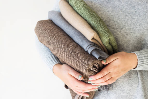 A stack of plaids and scarves in the hands of a woman in a gray sweater. Preparation in cold autumn and winter. Seasonal Wardrobe Concept A stack of plaids and scarves in the hands of a woman in a gray sweater. Preparation in cold autumn and winter. Seasonal Wardrobe Concept coat garment stock pictures, royalty-free photos & images