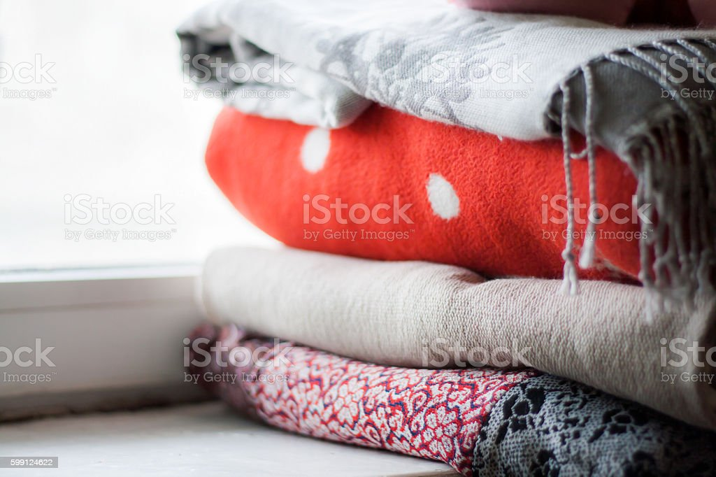 stack of plaids on the windowsill stock photo