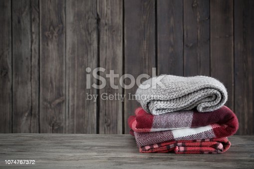 stack of plaids on old wooden background