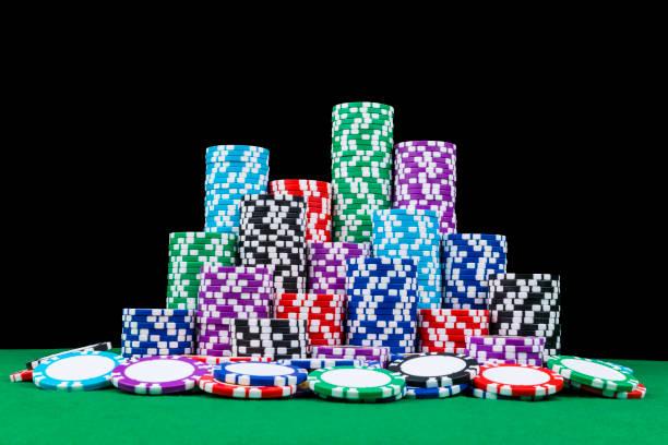 stapel von poker chips auf einem grünen poker spieltisch mit poker dice im casino. ein spiel mit würfeln. casino würfel konzept für unternehmerisches risiko, zufall, glück oder glücksspiel. chips und würfel für poker - filzunterlage stock-fotos und bilder